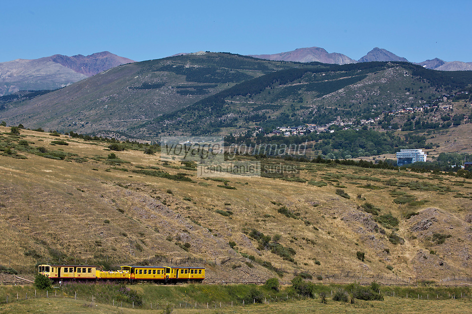 Europe/France/Languedoc-Roussillon/66/Pyrénées-Orientales/Cerdagne/Env de Saillagouse:  Traversant les paturages du plateau cerdan au Col Rigat, avec en fond: Font-Romeu-Odeillo-Via,  le Train jaune de Cerdagne appelé le Train Jaune ou le Canari, car les véhicules arborent les couleurs catalanes, le jaune et le rouge. relie la gare de Villefranche - Vernet-les-Bains à celle de Latour-de-Carol - Enveigt via Font-Romeu en suivant la vallée de la Têt puis en parcourant le plateau de Cerdagne.<br />  En fond Font-Romeu