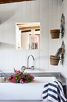 A chrome mixer tap above a Belfast sink set in a steel surround. Rustic pots on the wall hold a scrubbing brush.