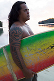 FRENCH POLYNESIA, Moorea. Portrait of Tattoo artist James Samuela holding a surfboard.