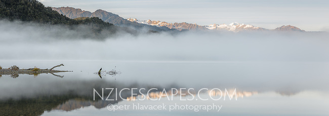 Morning fog and reflections at Lake Mapourika in winter. Morning light on Mount Tasman in distance, West Coast, Westland Tai Poutini National Park, UNESCO World Heritage Area, South Westland, New Zealand, NZ