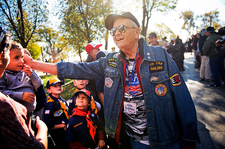UNITED STATES - NOVEMBER 11: U.S. Navy World War II veteran Rocky Tankersley, 92, from Kansas City, Mo., greets youngsters who were on hand to welcome Honor Flight vets to the World War II Memorial on Veterans Day.  (Photo By Tom Williams/CQ Roll Call)