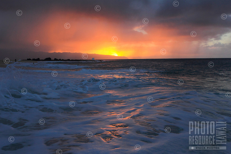 A misty sunset reflects through rain and off of seafoam at Ke Iki Beach on the North Shore of O'ahu.