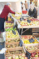 Apples of varying kinds in wooden crates for sale at a market stall at the market in Bergerac, a woman selling and a customer buying. Bergerac Dordogne France
