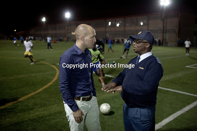 Khayelitsha, South Africa March 8, 2013: Amandla EduFootball founder  <br /> Florian Zech with police captain Nyaniso Mandlana on the field in Khayelitsha a poor township outside Cape Town, South Africa. They use football to initiate, support educational projects for youth in the township. The program keep children busy and it decreases the risk of them joining gang, criminal activity or teenage pregnancy. The crime level has decreased substantially in the area since the program was created in 2006. (Photo by: Per-Anders Pettersson)
