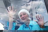 """Natasha<br /><br />Portraitserie von Obdachlosen in Kiew während der Corona Pandemie. Der Fotograf hat sie gebeten sich hinter dem Glas der Bahnhöfe fotografieren zu lassen. Er sagt: Ich porträtierte die Obdachlosen hinter dem Glas der Haltestellen und Unterführungen - das sind die Orte, an denen sie übernachten und leben. Das Glas ist aber auch symbolisch wie eine Wand zwischen uns und ihnen - wir sehen sie, aber wir hören sie nicht, sie sind wie Fische in Aquarien - isoliert von der Gesellschaft. Es ist nicht möglich, durch das Glas eine helfende Hand zu erreichen. Wir sympathisieren mit ihnen, wenn wir Ihnen während der Quarantäne von unseren Fenstern aus zuschauen, aber wir sind durch unsere komfortablen Wohnungen geschützt und sie blicken von unten zu unseren Fenstern hoch. / Portrait series of homeless people in Kiev during the Corona Pandemic. The photographer asked them to be photographed behind the glass of the train stations. He says: """"I portrayed the homeless behind the glass of the stations and underpasses - these are the places where they stay and live. But the glass is also symbolic like a wall between us and them - we see them but we don't hear them, they are like fish in aquariums - isolated from society. It is not possible to reach a helping hand through the glass. We sympathize with them when we watch them from our windows during quarantine, but we are protected by our comfortable apartments and they look up to our windows from below."""