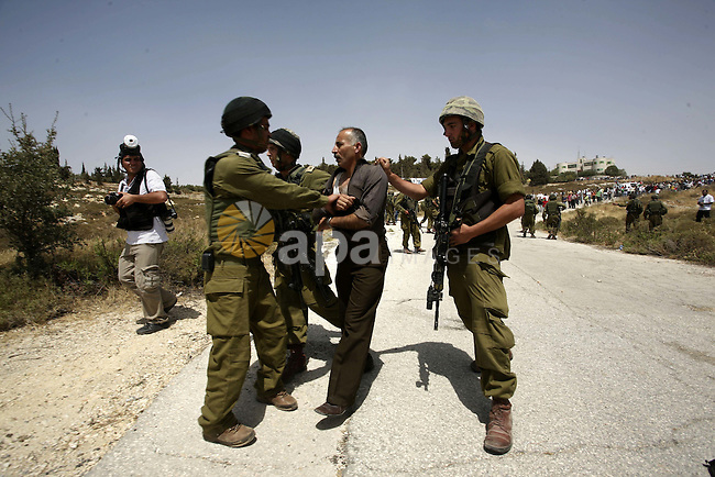 Israeli soldiers detain a Palestinian from the village of Bet In, north of Ramallah, as Palestinians protest against Israeli occupation on June 11, 2010 near the Jewish settlement of Beit El. Photo by Eyad Jadallah