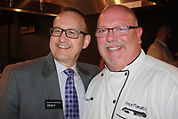 NWA Democrat-Gazette/CARIN SCHOPPMEYER Glenn Mack, Brightwater executive director (left), and Vince Pianalto, pastry and baking instructor, welcome guests to the Plant a Seed fundraiser April 28 at Brightwater in Bentonville.