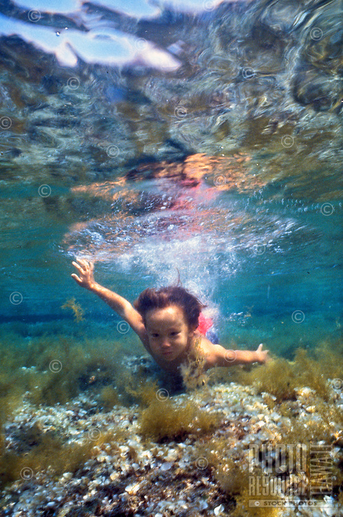 Little boy swimming underwater in tide pool at Honaunau