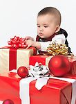 Six month old baby boy opening Christmas presents. Isolated on white background.