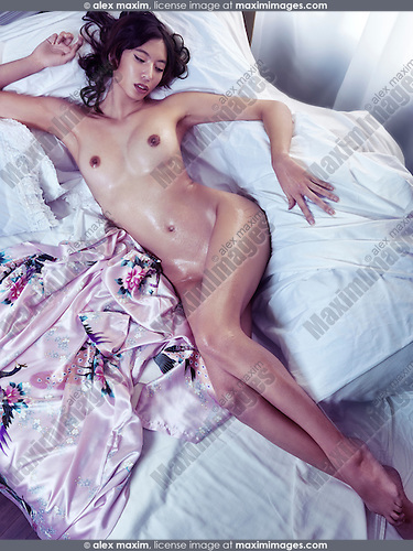 Beautiful nude asian woman with wet body and long legs lying undressed on a bed