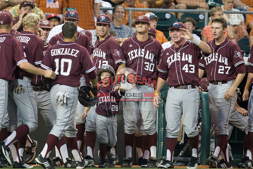 Texas A&M Aggies bench greets Kevin Gonzalez after he scored against the Texas Longhorns in NCAA Big XII Conference baseball on May 21, 2011 at Disch Falk Field in Austin, Texas. (Photo by Andrew Woolley / Four Seam Images)