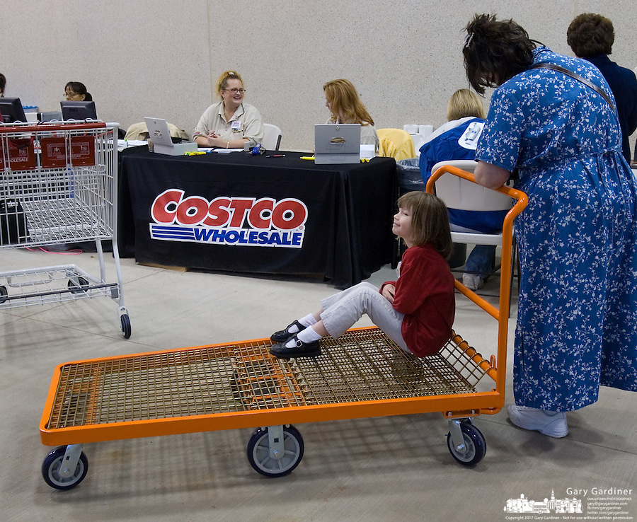 A child sits on a cart as her mother signs up for a card on the 623rd Costco Wholesale store opening in Columbus, Ohio, Wednesday, Nov. 29, 2006.<br />