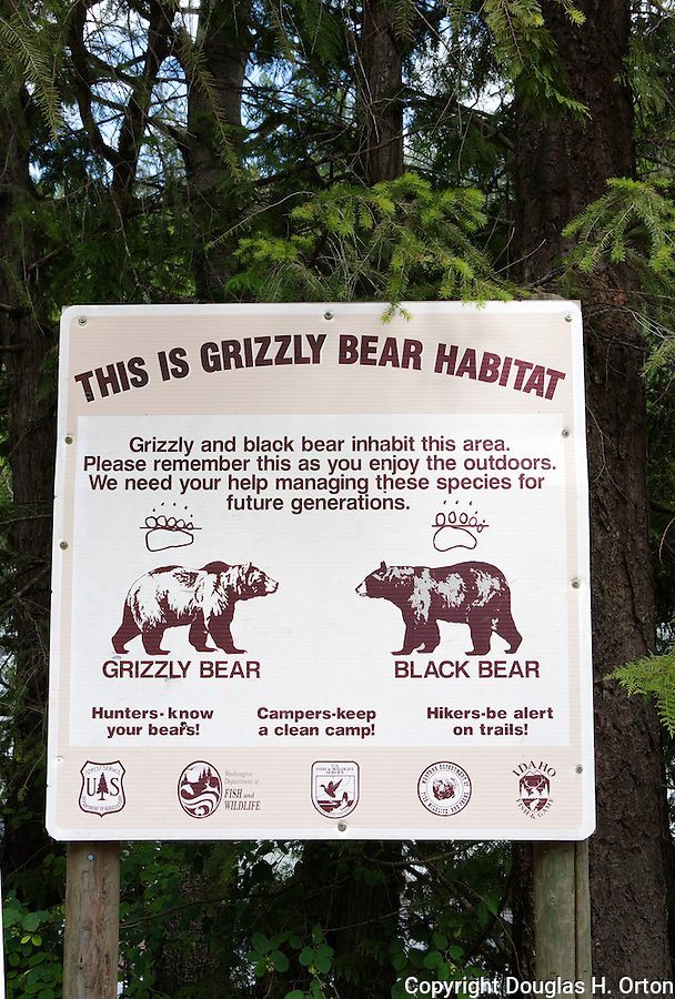 """Grizzly Bear sign along the Yaak River, Montana.  The Yaak River tumbles down steep valleys from Canada into the Northwest corner of the state of Montana.  Known in Canada as the Yahk, it originates in the Yahk Mouuntains, eventually draining to the Kootenai and Columbia Rivers in the United States.  """"I survived the Yaak"""" is a popular cry for those who manage to drive, bike, or drift the river in remote Montana."""