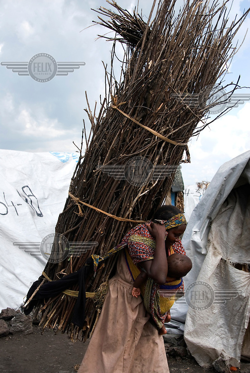 A mother with her baby strapped to her chest carries a large bundle of firewood back to her shelter in the Mugunga I IDP (Internally Displaced Persons) camp...
