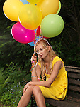 Young sad woman sitting on a bench with a bunch of colorful balloons