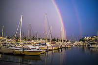 Fine Art Landscape Photograph of a double rainbow with water reflections in the ocean marina at Puerto Vallarta, Mexico.<br /> The lighting that day was spectacular as the setting sun cast a double rainbow over the marina. The variety of colours made this moment amazing.