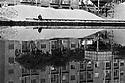 A man sat on the excavator rails, fishing at the dock of Navigli, behind him a pile of sand,  Milan, April 1970. Reflected in the water, a hopper for the sand. At the dock arrive the barges that carry sand from the river Ticino. © Carlo Cerchioli..Un uomo, seduto sui binari della scavatrice, pesca alla Darsena dei Navigli, dietro di lui un mucchio di sabbia, Milano, aprile 1970. Riflessa nell'acqua una tramoggia della sabbia. Alla Darsena arrivano i barconi che portano la sabbia dal fiume Ticino.