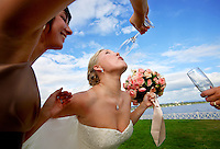 A bride keeps the veil of her wedding dress out the way as her bridesmaid puts a glass of champagne to her lips. (Photo by Scott Eklund/Red Box Pictures)