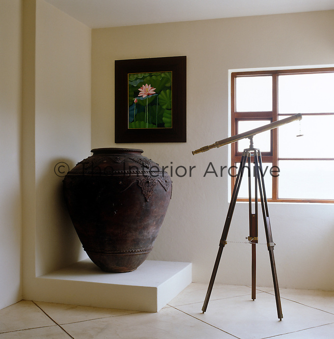 A large urn and a telescope on a tripod in a contemporary corner of the living room
