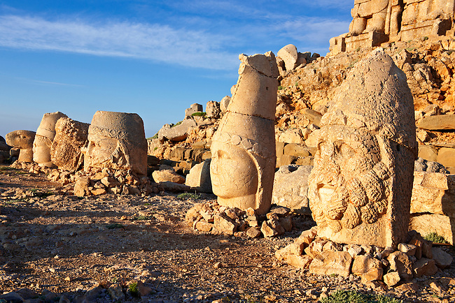 Pictures & Images of the statues of around the tomb of Commagene King Antochus 1 on the top of Mount Nemrut, Turkey. Stock photos & Photo art prints. In 62 BC, King Antiochus I Theos of Commagene built on the mountain top a tomb-sanctuary flanked by huge statues (8–9 m/26–30 ft high) of himself, two lions, two eagles and various Greek, Armenian, and Iranian gods. The photos show the broken statues on the  2,134 m (7,001 ft)  mountain. 2