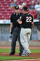 Quad Cities River Bandits manager Omar Lopez (22) argues a call with umpire Richard Riley during a game against the Cedar Rapids Kernels on August 18, 2014 at Perfect Game Field at Veterans Memorial Stadium in Cedar Rapids, Iowa.  Cedar Rapids defeated Quad Cities 5-3.  (Mike Janes/Four Seam Images)