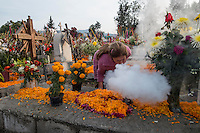 "A woman blows incense over the grave of a relative. Mexicans visiting their dead relatives, lighting candles, lighting incense and decorating their graves for the Day of the Dead festival in San Andre de Mixquic shot as part of the Sony RX100 III ""Celebrate The Streets"" series."