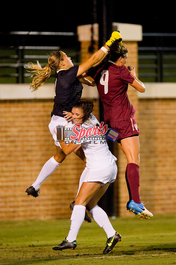 Wake Forest Demon Deacons goalie Aubrey Bledsoe (1) punches the ball away from Kassey Kallman (9) of the Florida State Seminoles at Spry Soccer Stadium on September 12, 2013 in Winston-Salem, North Carolina.  The Deacons and the Seminoles played to a 0-0 draw.   (Brian Westerholt/Sports On Film)