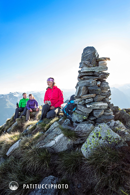 A group of hikers on the Punta di Spluga summit at sunset, laughing and talking, Valle Maggia, Ticino, Switzerland
