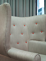 One of a pair of wing-backed armchairs in the suite living room is upholstered in a herringbone tweed punctuated with red buttons