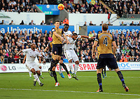 Laurent Koscielny of Arsenal heads the ball away from Bafetimbi Gomis and Ashley Williams of Swansea during the Barclays Premier League match between Swansea City and Arsenal at the Liberty Stadium, Swansea on October 31st 2015