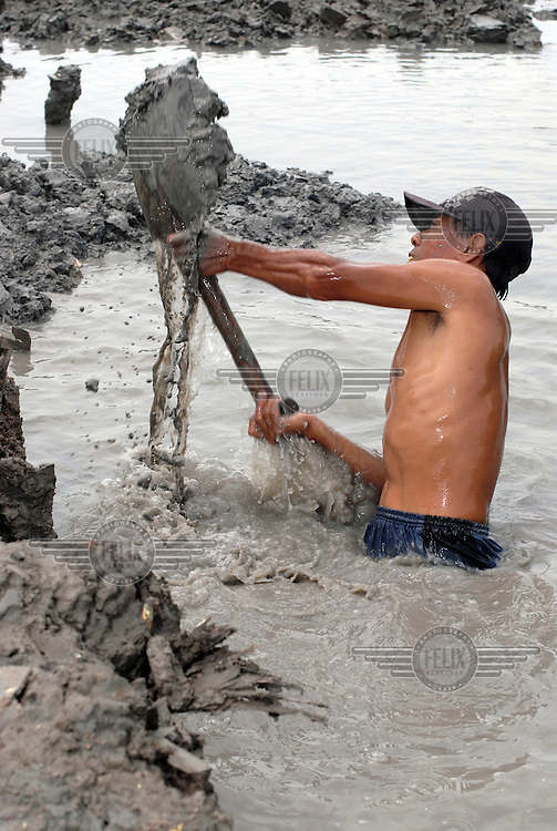 Former resident of Kedung Bendoh village digging in the ruins of his old home. Since May 2006, more than 10,000 people in the Porong subdistrict of Sidoarjo have been displaced by hot mud flowing from a natural gas well that was being drilled by the oil company Lapindo Brantas. The torrent of mud - up to 125,000 cubic metres per day - continued to flow three years later.