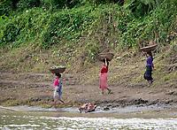 Women lading a boat at the Lay Mro River, Rakhine State, Myanmar