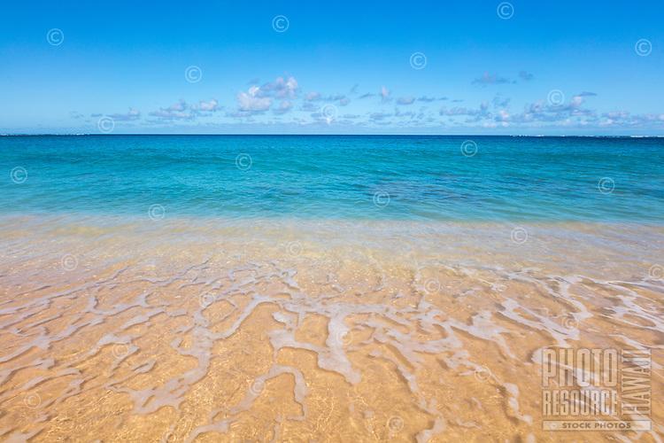 The turquoise blue and see through ocean water at Haena Beach, Kauai.