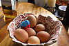 A clutch of eggs in a bowl with a little plastic chicken.<br />