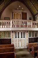 A delicately carved and gilded balustrade runs across one end of the Art and Crafts chapel, painted by Henry Payne who also created the stained glass windows