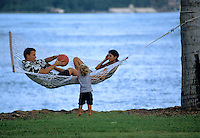 Family relaxing in hammock between palm trees with son, with ocean in background