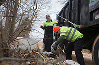 Teresa Sidwell, environmental manager (center) and Merced Cervantes, environmental officer (right) pick up discarded bags of Hydaul-EZ borehole stabilizer, Monday, February 10, 2020 along Logan Cave Rd. in Siloam Springs. Check out nwaonline.com/200211Daily/ for today's photo gallery.<br /> (NWA Democrat-Gazette/Charlie Kaijo)<br /> <br /> A cleanup crew from the Environmental Division for Benton County Government picked up illegally discarded waste products. <br /> <br /> Teresa Sidwell, environmental manager, said a lot of times people are trying to avoid having to pay to take it to the land fill, but added, they have a program where people can drop off large waster products for free.
