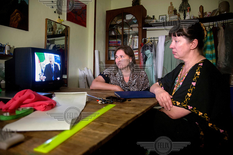 The television broadcasts a news item about President Lukashenko as two women, a dress maker and her client, discuss an order.