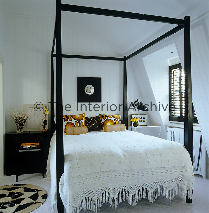 The guest bedroom has a black four-poster bed and is decorated in a strking black and white colour scheme