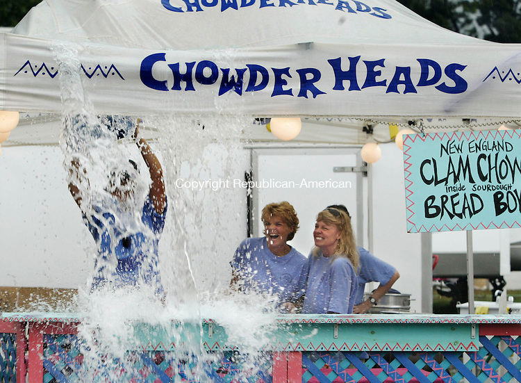 TERRYVILLE,  CT 17 September 2005 -091705BZ14- After a heavy rain soaked the Terryville Fair Saturday Chowderheads owner Amy Hofmann (CQ), of Morris, used a small stool to push water off the tent as Rae Cameron, of New Hartford, Debbie Bennett, of Litchfield, and Margaret Gaynor, of Litchfield, reacted to the splash. Chowderheads sells New England Clam Chowder in a bread bowl.<br /> <br />  Jamison C. Bazinet / Republican-American