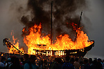 Donggang, Taiwan -- The King Boat on its last voyage is set on fire and slowly burns to ashes in a searing blaze at the beach.