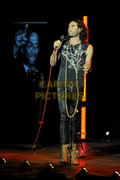 Russell Brand performing his 'Messiah Complex' Show, Eventim Apollo, Hammersmith, London, England. <br /> 14th October 2013<br /> on stage in concert live gig performance full length black sleeveless top leather trousers scarf beard facial hair necklace <br /> CAP/MAR<br /> &copy; Martin Harris/Capital Pictures