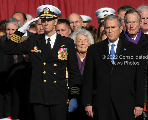 Norfolk, VA - January 10, 2009 -- Captain Kevin E. O'Flaherty, left, commanding officer of the aircraft carrier USS George H.W. Bush (CVN 77), stands next to President George W. Bush during a 21-gun salute during the commissioning ceremony of the aircraft carrier USS George H.W. Bush (CVN 77) at Naval Station Norfolk, Va. The Navy's newest, and final, Nimitz-class aircraft carrier is named after World War II naval aviator and the 41st president of the United States George H.W. Bush. .Credit: Micah P. Blechner - U.S. Navy via CNP
