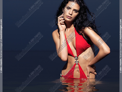 Beautiful young woman in red swim suit standing in water. High fashion photo.