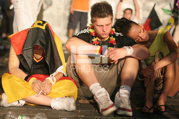 German national soccer team supporters at the Fan Festival next to the Brandenburg Gate in Berlin Germany, on July 4th, 2006 react to the loss of Germany against Italy in extra time. The FIFA World Cup Semi-Final match was won on two late goals in extra-time by Italy, which defeated Germany to advance to the final.