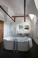 A large contemporary free-standing bath takes centre stage in this beamed bathroom