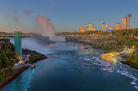 A view of the Niagara River including the American Falls, Horseshoe Falls, and skyline of Niagara Falls, Ontario just before sunrise.