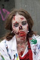 Female participant in the prague Zombi walk in may 2014. Headshot looking at the camera, wearing red blouse and a white smock, with different colors on it, having blood in her face.