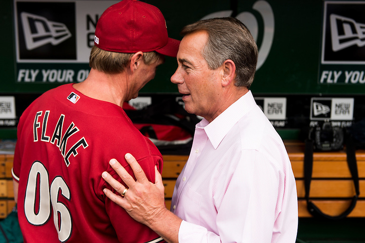 UNITED STATES - JUNE 13: Sen. Jeff Flake, R-Ariz., gets a pep talk from Speaker of the House John Boehner, R-Ohio, in the Republicans' dugout before the 52nd annual Congressional Baseball Game at national Stadium in Washington on Thursday, June 13, 2013. (Photo By Bill Clark/CQ Roll Call)