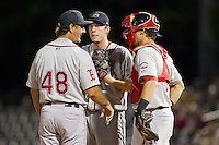 Greenville Drive starting pitcher Teddy Stankiewicz (19) listens intently as Greenville Drive pitching coach Paul Abbott (48) makes a mound visit along with catcher Jordan Weems (18) during the game against the Charleston RiverDogs at Joseph P. Riley, Jr. Park on May 26, 2014 in Charleston, South Carolina.  The Drive defeated the RiverDogs 11-3.  (Brian Westerholt/Four Seam Images)